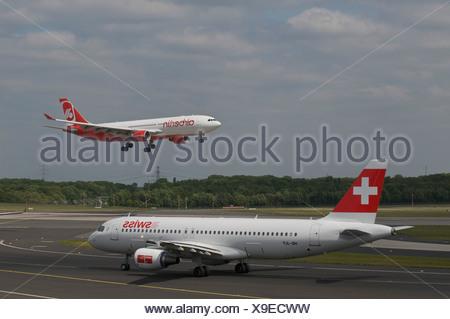 Passenger airplane of Swiss International Air Lines Ltd. on the runway, behind an airberlin airplane departing, Duesseldorf - Stock Photo