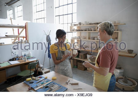 Female potters discussing pottery in art studio - Stock Photo