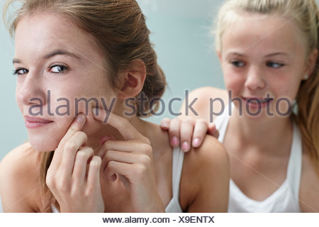 Girl squeezing a spot, friend with hand on shoulder - Stock Photo