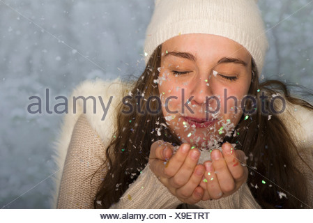 Young woman wearing winter clothing, blowing handful of confetti - Stock Photo