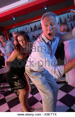 Senior Man Dancing With Younger Woman In Busy Bar - Stock Photo