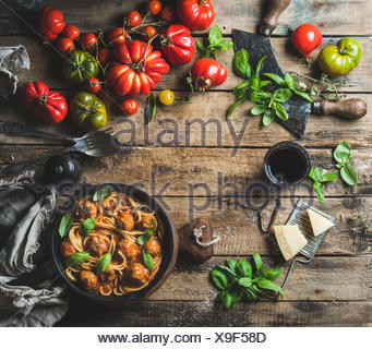 Italian pasta spaghetti with tomato sauce and meatballs in cast iron pan served with Parmesan cheese, fresh basil leaves and tom - Stock Photo
