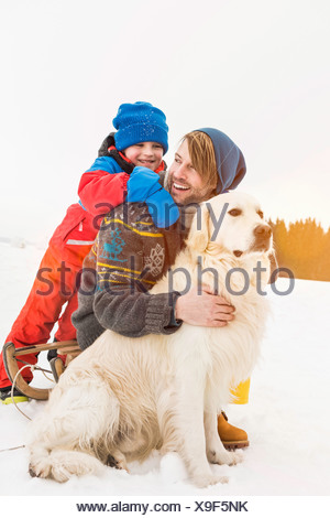 Father and son with dog in snow - Stock Photo