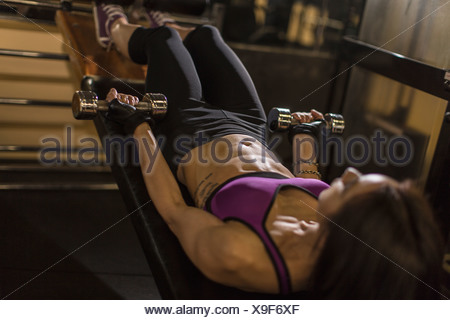 Mid adult woman using dumbbells on weight bench - Stock Photo