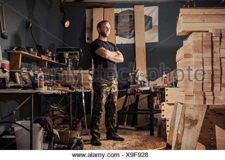 Portrait of mid adult man in carpenter workshop - Stock Photo