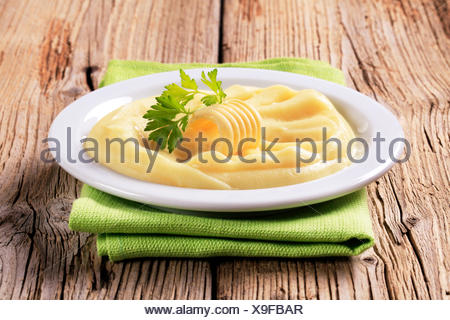 Mashed potato and a curl of fresh butter - Stock Photo