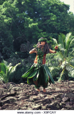 Young hula dancer in ti leaf skirt at Hawaiian heiau ( temple site ) performing a hula with maile lei - Stock Photo