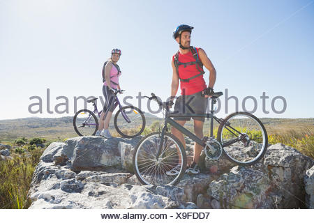 Fit cyclist couple standing at the summit looking around - Stock Photo