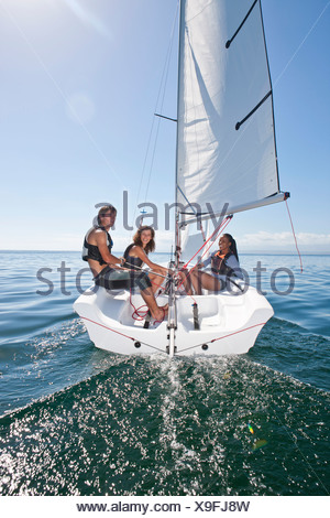 Three young friends relaxing on sailboat - Stock Photo