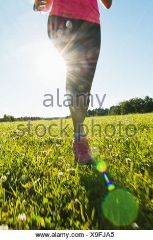 Low section of woman jogging in meadow - Stock Photo