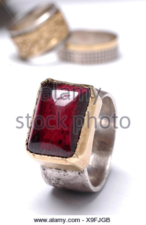 Ruby on a silver ring on white background with wedding rings in the background - Stock Photo