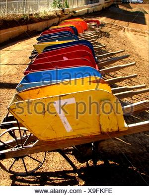 Multi colored wood wheelbarrows are lined up for the Johnny Studebaker Race at the El Dorado County Fairgrounds in Placerville, California. - Stock Photo