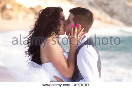 Groom kissing his bride on beach - Stock Photo