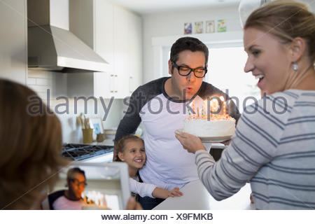 Father blowing out birthday cake candles in kitchen - Stock Photo
