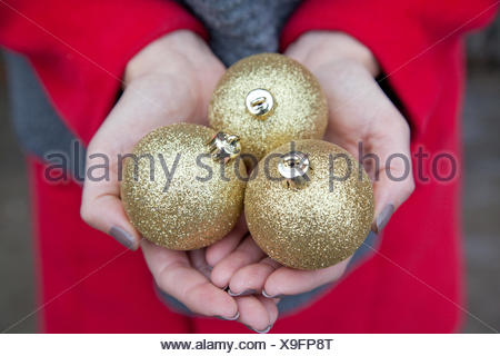 Close up of woman's hands holding three Christmas baubles - Stock Photo