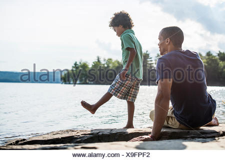 A father and son on a lake shore in summer. - Stock Photo