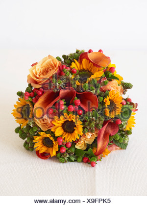 Bunch of flowers including sunflowers, roses and berries, close-up - Stock Photo