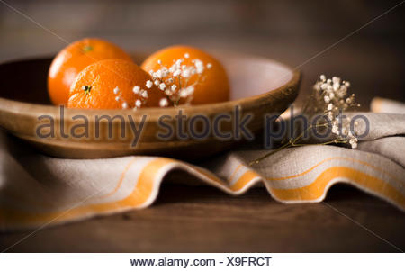 3 ripe oranges in a rustic wooden bowl with linen and flowers. - Stock Photo
