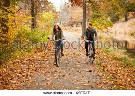 Happy young couple cycling on riverside in autumn - Stock Photo