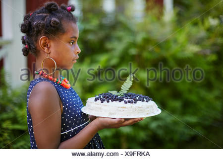 Girl holding cake with blueberries - Stock Photo