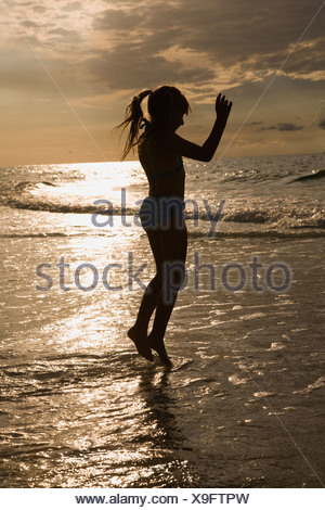 Girl in ocean surf at sunset, Florida, United States - Stock Photo