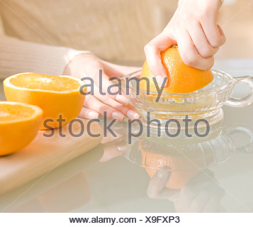 Woman squeezing oranges - Stock Photo