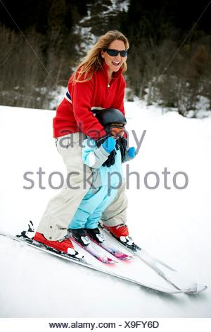 Male toddler in front of mother skiing downhill, Les Arcs,Villaroger,Savoie,France - Stock Photo