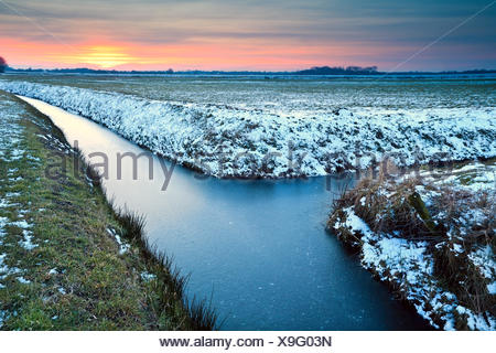 sunset over winter meadows - Stock Photo