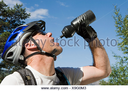Mountain biker drinking from bottle - Stock Photo