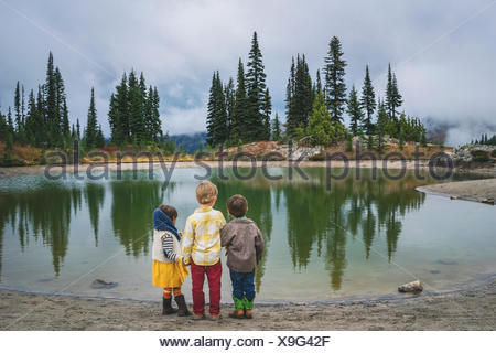 Rear view of two boys and a girl standing by lake - Stock Photo