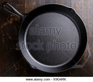 Black cast iron empty frying pan on wooden background - Stock Photo