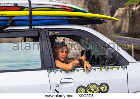 Teenage girl sitting in car with surfboard. - Stock Photo
