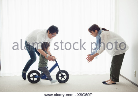 Parents with son learning to ride bicycle - Stock Photo