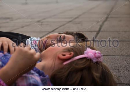 Two girls lying on ground talking - Stock Photo