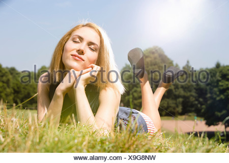 Young woman enjoying sunshine in park - Stock Photo
