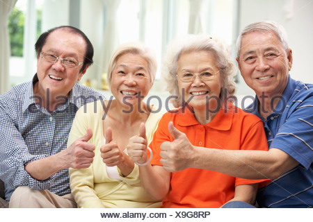 Group Of Senior Chinese Friends Relaxing On Sofa At Home - Stock Photo