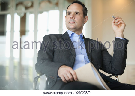 Thoughtful businessman sitting in chair - Stock Photo