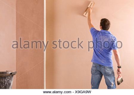 Man plastering wall in house - Stock Photo