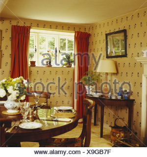 Antique table set for lunch in cottage dining room with cream patterned wallpaper and small window with red curtains - Stock Photo