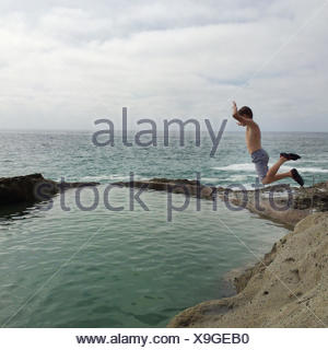 Boy jumping into natural pool on beach, California, america, USA - Stock Photo