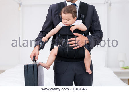 Midsection of father carrying baby while holding briefcase - Stock Photo