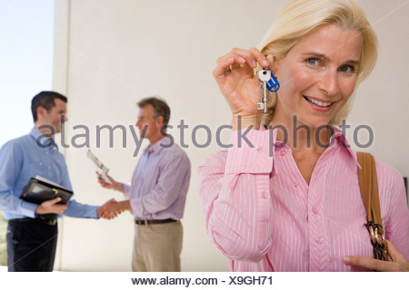 Mature woman holding up house keys, smiling, portrait, two men shaking hands in background - Stock Photo