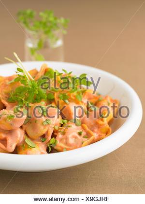 Tortelloni in creamy tomato sauce - Stock Photo
