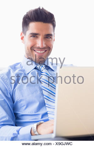 Happy businessman on couch using his laptop - Stock Photo