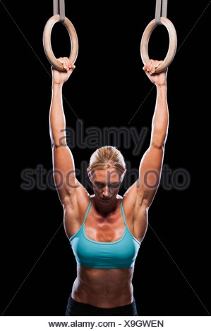 Woman using exercise rings - Stock Photo
