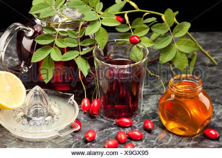 Hagebuttentee mit Honig und Zitrone im Glas - Stock Photo