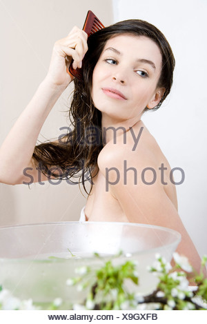 woman combing wet hair - Stock Photo