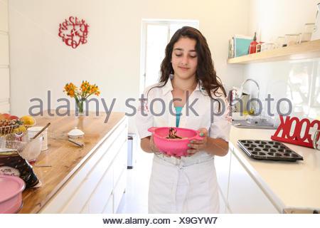Teenage girl in white apron baking cake in kitchen - Stock Photo