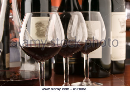 Three red wine glasses and bottles - Stock Photo