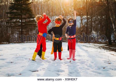 Three children standing on frozen lake wearing superhero costumes - Stock Photo